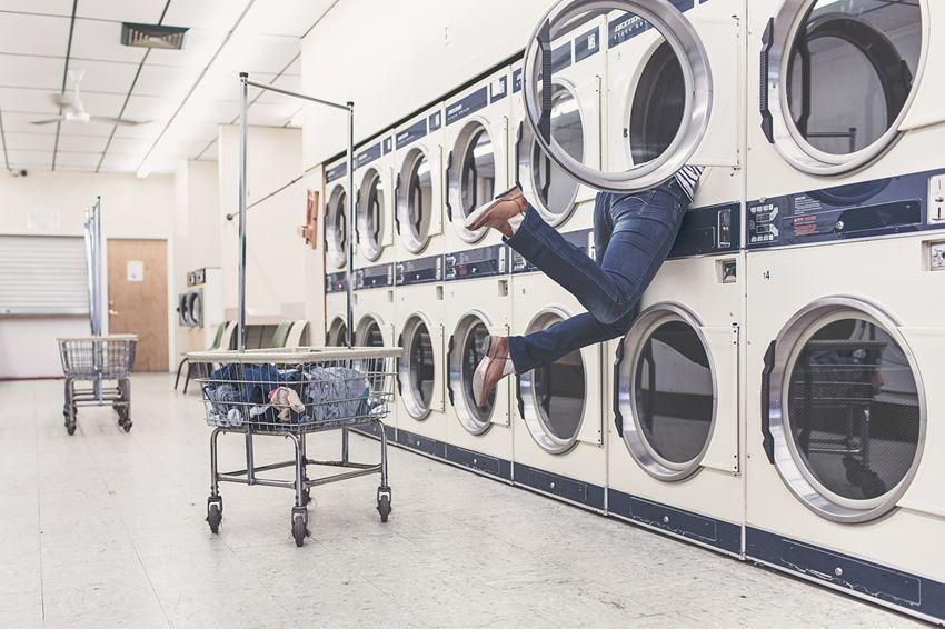 Person hängt sich im Waschsalon in eine der Waschmaschinen rein